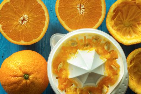Squeezing orange juice , oranges with manual hand juicer on rustic table , closeup , top view Standard-Bild - 107346278