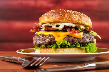 Bacon cheese burger on plate with homemade brioche bun  , red wooden log background Standard-Bild - 107346284