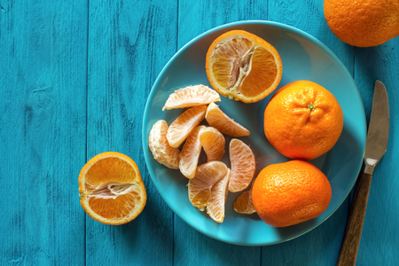 Ripe clementines with plate on rustic turquoise wooden table with copy space , top view Standard-Bild - 107346283