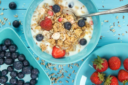 Muesli and yogurt breakfast with strawberries , blueberries and seeds closeup on painted wooden table Standard-Bild - 107346289