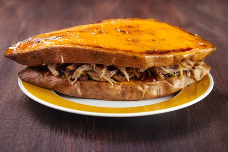Sandwich made of two owen roasted sweet potato slices and pulled pork with sauce on plate Standard-Bild - 107305635