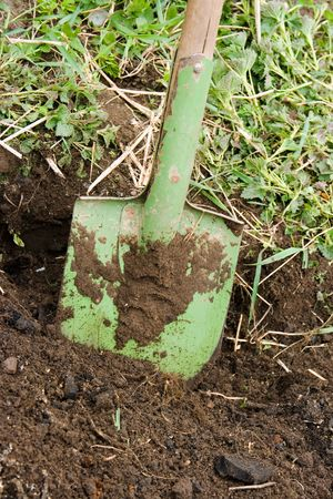 toil: Green metallic shovel in the black ground
