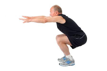 squat: Fit senior man doing a squat