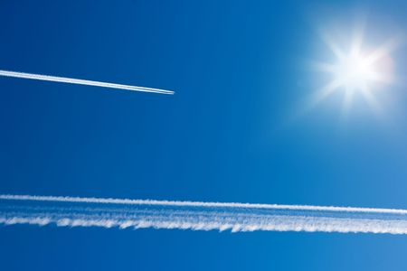 Airplane tracks and sun in the blue sky Stock Photo - 4877562