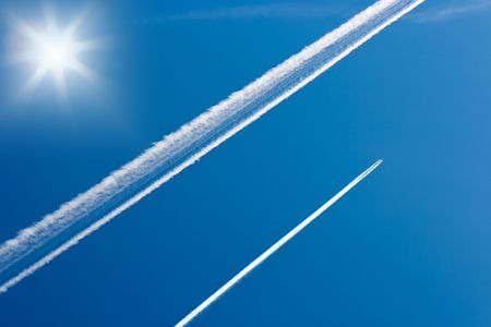single line: Sun and airplane tracks in the sky Stock Photo