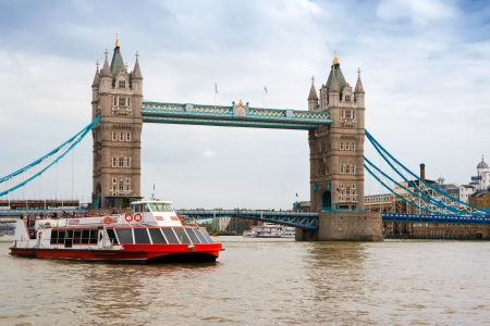 goes: A sightseeing boat goes near the Tower Bridge. London, England