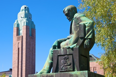 national poet: Statue of Aleksis Kivi and the tower of Helsinki railway station. Finland Stock Photo