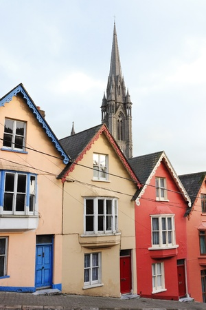 Terraced houses with the St. Colman's cathedral in the background. Cobh, County Cork, Ireland  photo