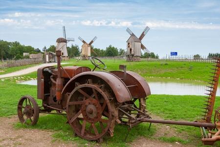 old tractors: Old tractor and wooden windmills in Angla  Saaremaa island, Estonia  Europe