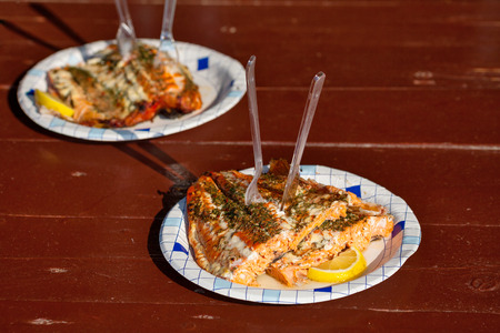 Grilled salmon with lemon on a paper plate  Outdoor setting photo