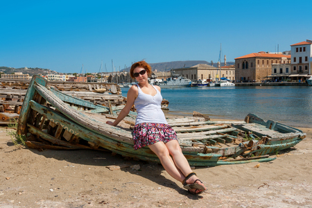 marina bay sand: Young girl sits on old boat in harbour of Chania. Crete, Greece