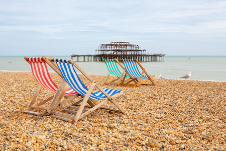 old pier: Deckhairs on Brighton beach with West Pier behind. Brighton, East Sussex, England