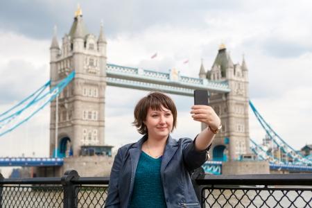 若い女性はタワー ブリッジの前で自分の写真を撮るします。ロンドン、イギリス