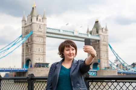 Young woman taking a photo of herself in front of the Tower Bridge. London, England Stock Photo