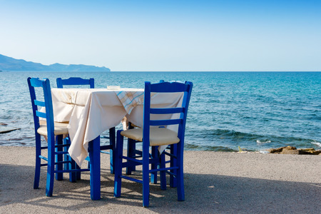 Table and chairs in sidewalk cafe at Kissamos, Crete, Greece  Stock Photo