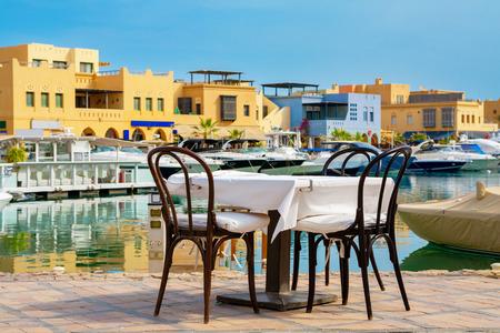 Table and chairs in sidewalk cafe at Abu Tig Marina. El Gouna, Red Sea, Egypt  photo