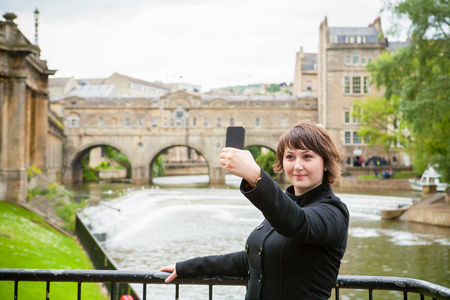 Young woman taking a photo of herself in front of Pulteney Bridge. Bath, Somerset, England, UK photo