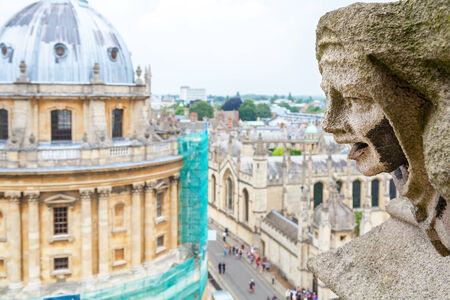 Carved Gargoyle Figure and Radcliffe Camera from St. Mary The Virgins Church. Oxford, England, UK