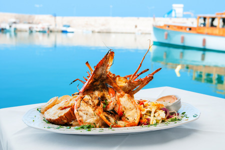 seafood dinner: Lobster served with vegetables on white plate. Rethymno, Crete, Greece