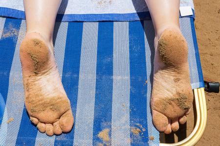 sandy feet: Sandy feet of girl laying on sunbed