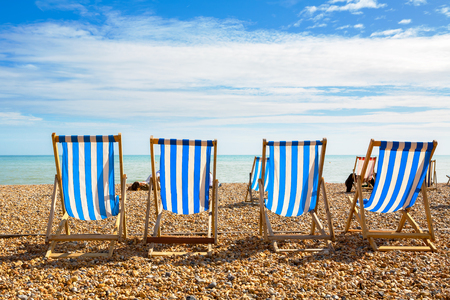 Pebble Beach: Deckchairs on Brighton beach. Brighton, East Sussex, England
