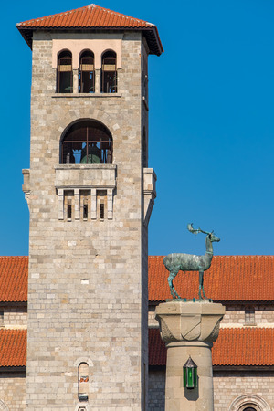 dodecanese: Bell tower of Church of the Evangelismos (Annunciation) and Deer statue at Mandraki harbour. Rhodes town, Rhodes, Dodecanese islands, Greece