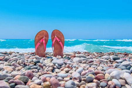 Pair of flip flops on pebble beach. Rhodes, Greece
