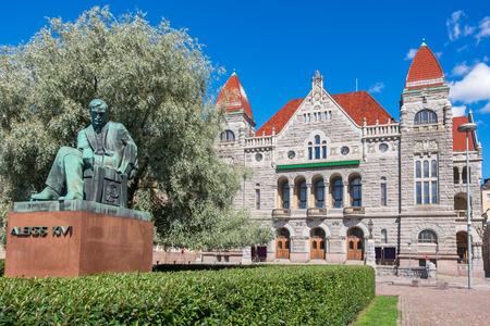 Statue of writer Aleksis Kivi (1834-1872) and Finnish National Theatre. Helsinki, Finland Editorial