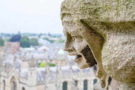 Carved Gargoyle Figure and All Souls College from St. Mary The Virgins Church. Oxford, England, UK Archivio Fotografico