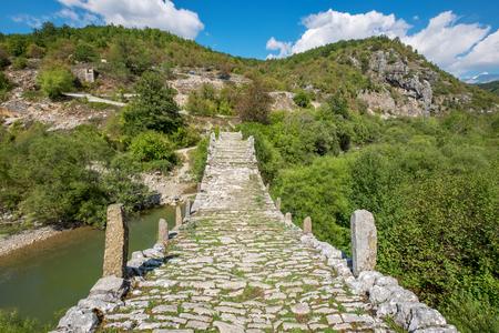 Three arches stone bridge of Kalogeriko (or Plakida) on the river of Voidomatis. Central Zagoria, Epirus, Greece Stock Photo