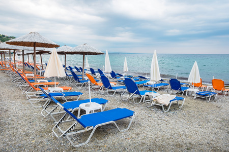 greece shoreline: Beach umbrellas and empty lounge chairs on a cloudy day. Platamonas, Pieria, Macedonia, Greece, Europe