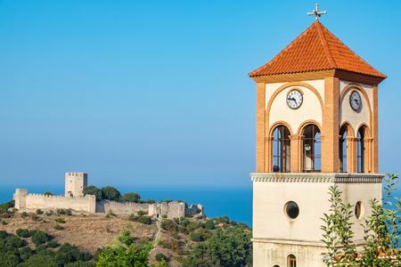 panteleimon: Bell Tower of the church of Agios Eleftherios in Neos Panteleimonas village and medieval fortress of Platamonas in the distance. Pieria, Macedonia, Greece Stock Photo