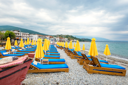 Beach umbrellas and empty lounge chairs on a cloudy day. Platamonas, Pieria, Macedonia, Greece