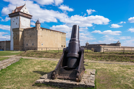 herman: Old cannon and Hermann castle in Narva fortress. Estonia, Europe. Russian fortress Ivangorod at the distance
