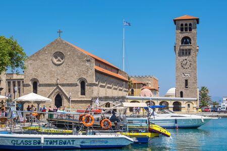 RHODES, GREECE - JULY 4, 2015: Tourists walking on quay of Mandraki harbour near Church of the Evangelismos (Annunciation)