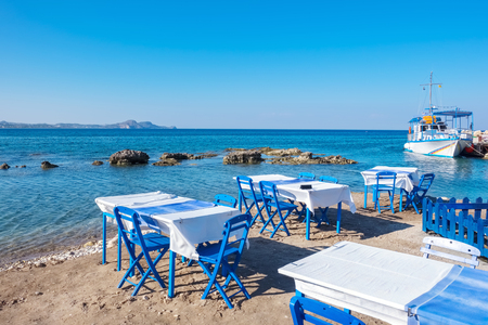 Beach with traditional blue tables and chairs. Kolymbia. Rhodes, Greece