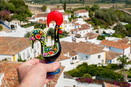 Male hand holds a Rooster of Barcelos (Galo de Barcelos) above Obidos. Portugal