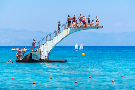 RHODES, GREECE - JULY 4, 2015: Many people having fun on diving board at Elli Beach, the main beach of Rhodes Town Editorial