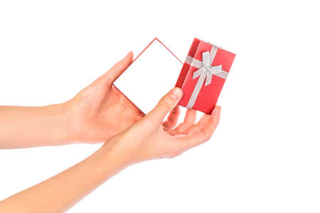 Opening a red box. Image with white background. Christmas gift and female hands on a sultry background.
