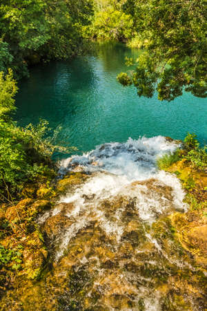 View from above the waterfall. Water falling into the green lake. A lake among trees in Krka pitch in Croatia.