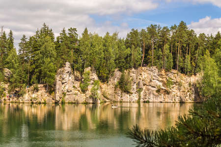Lake and rock cliffs overgrown by forest. Tourist attraction in the Rock Town in the Czech Republic.