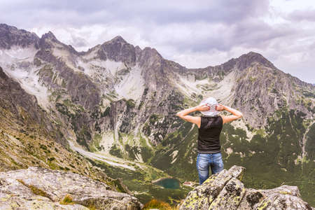 Mountain landscapes in the Slovak Tatra Mountains. A woman observing from the top, a mountain valley. Standard-Bild