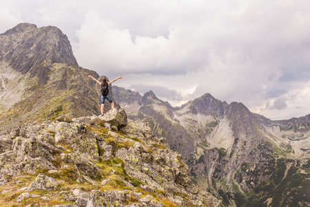 Tatra mountains landscape with a coming storm. A woman who enjoys climbing a mountain peak.