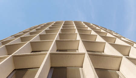 Urban architecture - the symmetry of the building against the sky. A convergent perspective, created by the facade of the building.