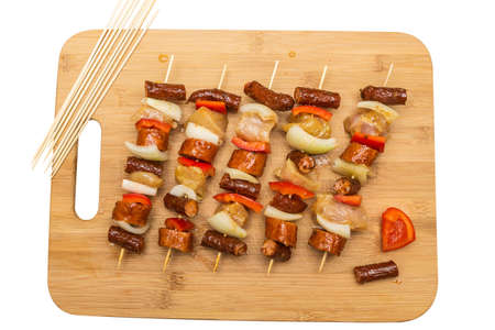 Homemade shashlik stacked on a wooden chopping board. Skewers of kabanosy, chicken and vegetables.
