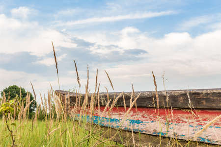 A colorful boat pulled to the shore. Colorful hull of old boat standing on a meadow. Landscape with sky. Standard-Bild