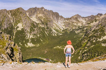 A woman admiring a mountain landscape. Slovak Tatra Mountains and the view of the Mengusovska valley. Tourist in the mountains.