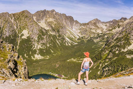 Mountain landscapes in the Slovak Tatra Mountains. A woman on a tourist trail observing the mountain valley.