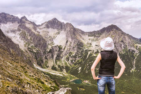 A woman at the top of the mountain, admiring mountain scenery. Tatra mountains landscape from the summit. Standard-Bild