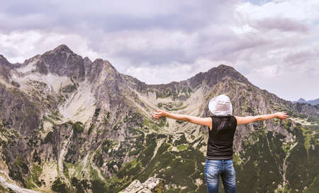 Tatra mountains in Slovakia. Mountain landscape with a woman enjoying the summit. Mountain landscapes in the Tatras.